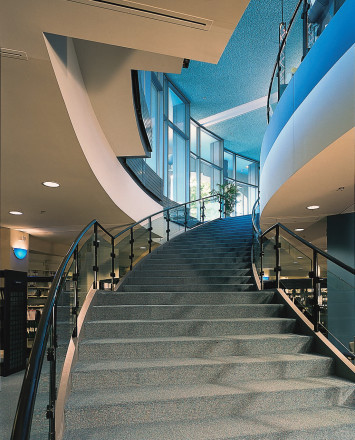 Upward angle of curved Hewi guardrail with clear glass infill at the Kalamazoo Public Library, MI.
