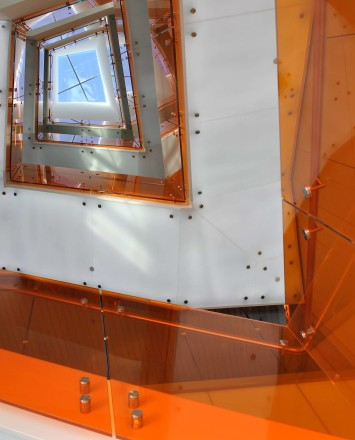 Skyward view of spiraling Optik guardrail with orange colored glass infill at UC Berkley's Helios Building, CA.