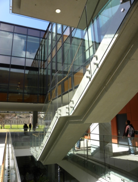 Outdoor under-stairwell view at the University of California San Diego, CA, Optik guardrail with clear glass and wood handrail