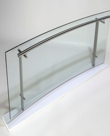 Segment of Konic curved guardrail with glass infill in a studio.