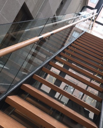 Glass staircase baffles with wooden handrail
