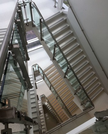 View down a stairwell of Inox guardrail with clear glass infill.