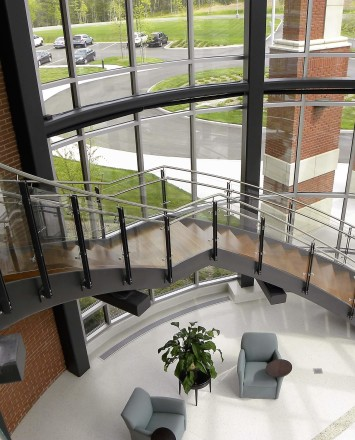 Ferric curved guardrail with glass infill installation at Clare Rose Corp., NY.