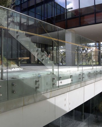 Outdoors side angled view at University of California San Diego, CA, Optik guardrail with clear glass and wood handrail