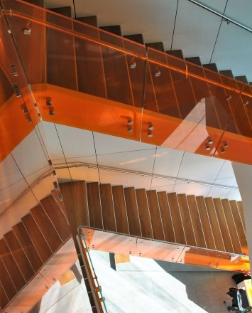 Angled view at University of California Berkley, Helios building, CA, Optik guardrail with orange tinted glass and stainless steel handrail