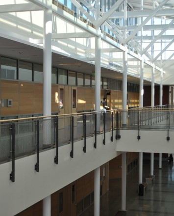 Ferric guardrail with wood top rail and woven mesh infill panels at De Anza College, CA.