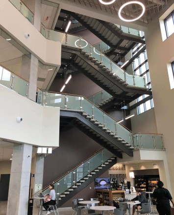 Circum guardrail installation with wood handrail and frosted glass infill at Texas State University, TX.