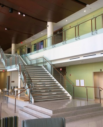 Atrium stair at University of Wisconsin School of Nursing, Kubit glass railing with wood top rail and posts.