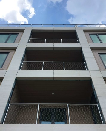 Circum round guardrail with stainless steel infill mesh attached via cable infill rail at Monroe Condominiums, NJ.