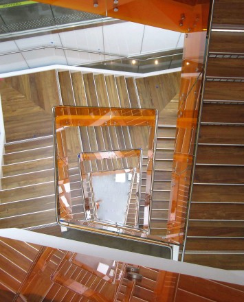 View of stair well with Optik guardrail and orange colored glass infill at UC Berkley's Helios Building, CA.