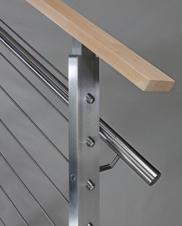Closeup of stainless steel metal infill railing connection with wooden top rail