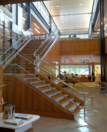 Upward view of open stairwell at Los Gatos Library, Optik Shoe with wood handrails and custom shelf