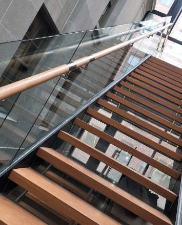 Glass staircase guardrail with wooden handrail