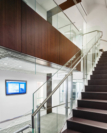 Upward view of white & wood staircase Smoke baffle system with Konic railing system